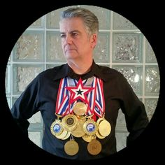 Brad Byers, world-renowned sword swallower / sideshow performer, with world record medals. Brad is a 59 time world record holder!