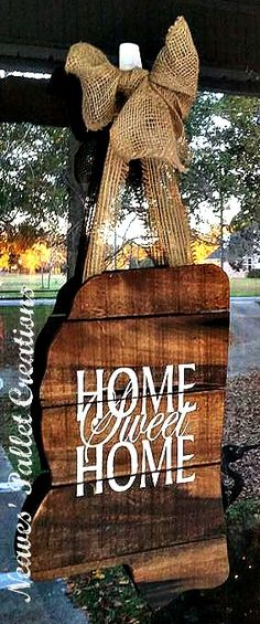 """RECYCLED WOOD PALLETS: This was a custom ordered Door Hanger. It is the outline of the state of Mississippi, stained with a hand painted """"Home Sweet Home"""" in the middle of it. It has a Burlap bow and hanger. It is 11"""" x 17"""" and has total hanging length of 27"""". We are selling this for $28. This one has been taken, but let us know if you want to give one as a gift or get it for yourself.  Item # 805"""