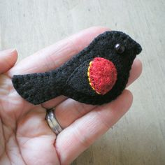 One of my favorite birds, the red-winged blackbird.  Here he's a harmless wool brooch.  In the swamp, he's the master divebomber.