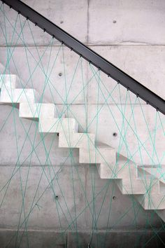 Concrete stair case with string/cord hand railing by MO Architekten