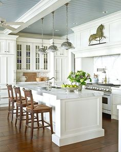 Gorgeous antique furniture + La Cornue Range         Kitchen seating       white + wood contrast / seating in the kitchen / exposed beam...