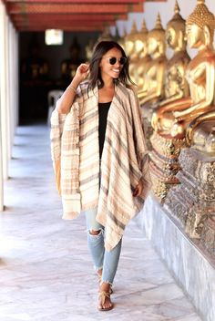 Street Style - The Top Blogger Looks Of The Week: Fashion Blogger 'Wait You Need This' wearing a beige stripe poncho, a black tank top, light distressed skinny jeans, nude sandals and round aviator sunglasses. Summer outfit, spring outfit, comfy outfit, travel outfit, vacation outfit, casual outfit.
