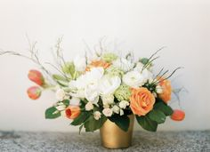 gold vases filled with orange and white florals Photography by André Teixeira from Brancoprata / brancoprata.com