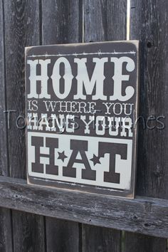 Handmade, painted, and distressed wooden sign that says home is where you hang your hat. It measures 11in x 11in and has a stainless steel wire in