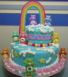 Fondant 2 tier cake....I like the blue and clouds, with carebears around it...and a rainbow.
