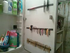 Magnetic strips inside the bathroom medicine cabinet mirror...(HOW DID I NOT THINK OF THIS! -Nik)