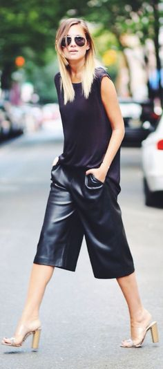 Danielle of style blog We Wore What pairs Zara black leather culottes with an H&M tank and Guess? lucite and snakeskin slides.