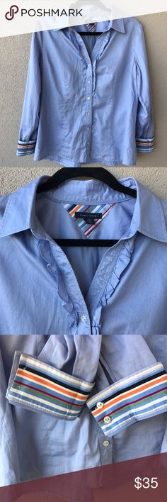 """Tommy Hilfiger Blue Ruffle Striped Cuff Blouse Classic light blue button-down collared shirt with a twist.  This top has feminine ruffle detailing and colorful stripes on the sleeve cuffs and under the collar for a pop of fun, along with pleated details in the back.  Excellent used condition; only flaw is fabric tag cut off for comfort.   - Size Large L  - Approx. 21"""" armpit to armpit - Approx. 25.5"""" shoulder to hem  - Closet ID # 0123 Tommy Hilfiger Tops Button Down Shirts"""