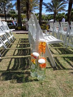 Trio of cylinder vases with orange Mokara Orchids, Mango Calla Lilies, and orange Gerbera Daisies. Designed by China Rose Florist, Marco Island, Fl.