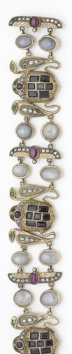 A mid 19th century gem-set archaeological revival bracelet  The scarab-shaped plaques set with step-cut sapphires, cabochon rubies, rose-cut diamonds and circular-cut emeralds, each flanked by two cobras decorated with rose-cut diamonds and circular-cut emeralds, interspersed with oval star sapphires and winged scarabs accented with oval cabochon rubies and rose-cut diamonds, the reverse with engraved detail, mounted in silver and gold, length 18.5cm