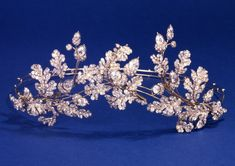Ca. 1855.  Tiara of oak-leaves and acorns. Silver and gold, open-back, set with diamonds and convertible to a brooch or combs. Case labelled Hunt & Roskell, New Bond Street. Holds 2 tortoise-shell combs and gold frames for the tiara and brooch. The jewelled elements are interchangeable between the combs, the brooch-frame and tiara.