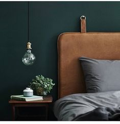 Headboard in leather, with belt loops attached to the wall. Stylish solution with grey bedding & with a contrasting dark wall colour. Nice with the hanging bedside table lamp & simple styl…