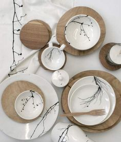 Collection of hand carved wooden plates and white crockery with bird and branch…