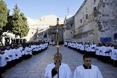 A member of the clergy holds a cross as he waits for the arrival of the Latin Patriarch of Jerusalem Fouad Twal outside the Church of the Nativity, the site revered as the birthplace of Jesus, in the West Bank city of Bethlehem.