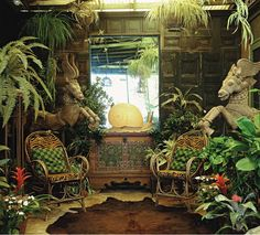 """The covered porch at Frogmore looks more like a tropical altar than a place to sit in rocking chairs. To create such an extravagant space, Duquette paneled a wall and decorated with an antique Austrian trunk topped with """"Ghost Snail,"""" one of his designs. The pair of carved wooden horses is from India and has carved wings that he added. Completing the jungle vibe: lush foliage and antique Adirondack twig chairs upholstered in tiger-printed corduroy."""