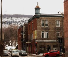Montreal. Northwest corner of Duluth and St. Urbain.    Built: 1900.  Building occupying a corner and wearing a small corner tower (watch tower).  Early twentieth century, when this building was built, we took the cable car nearby. This led us to a belvedere on Mount Royal is seen here in the background.