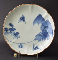 A 17th century Japanese blue and white porcelain dish, Japanese, Arita or Kakiemon kilns c.1680-1700. The thickly potted flower shaped porcelain dish is painted with a rustic dwelling under the shelter of a willow tree. There are two dear either side of a rope. The rim is dressed with Kuchibeni (Meaning lipstick) iron-oxide glaze. The Reverse with painted Karakusa scrolling foliage, the base with a running Fuku mark (Luck).
