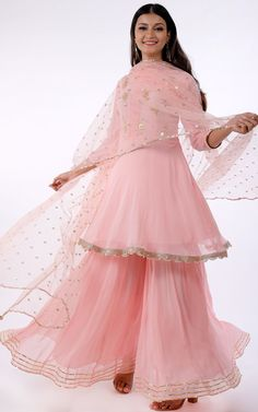 Light Pink Gota Patti Frock Style Sharara Set Description: Golden Gota Patti floral motifs sprinkled all-over the bodice Three-quarter sleeves Boat neck with pintucks detailing in the centre front A-line short Kurti Pattern with gota lace b Frock Fashion, Indian Fashion Dresses, Indian Gowns Dresses, Dress Indian Style, Indian Designer Outfits, Pakistani Dresses, Shadi Dresses, Pakistani Bridal, Indian Bridal