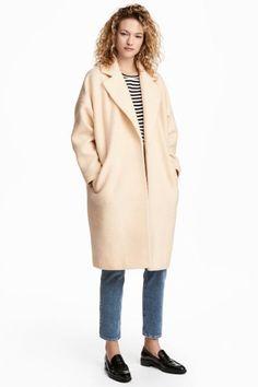 Пальто из смесовой шерсти с воротником и лацканами, а также заниженной линией плеча. Боковые карманы. Без застежки. На подкладке.