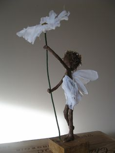 This little daisy fairy stands at from bottom of the base to the top of the daisy. The fairy herself is A sweet little fairy peeping around a daisy, with a dress made of white and pink scrim. Paper Mache Sculpture, Sculpture Art, Daisy, Ideias Diy, Paperclay, Flower Fairies, Fairy Dolls, Wire Art, Stone Art