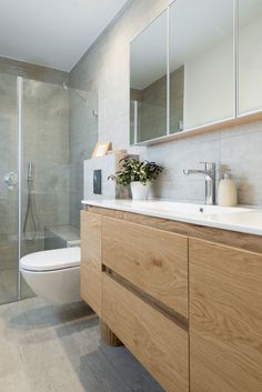 In this modern ensuite bathroom there is a glass surround shower with light colored tile. The wood cabinets and drawers below the white sink provide plenty of storage for toiletries.