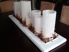 Picture frame or mirror centerpieces with candles in vases.