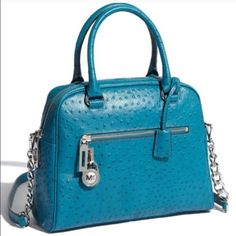 """💙 MK Kors Satchel ostrich leather turquoise purse Michael Kors MK Joan Large Satchel - ostrich leather - turquoise blue purse bag cross body satchel handbag.  Silver MK lock and key Silver Hardware, top handles with rings, chain detail remobeable shoulder strap.  Front zip pocket, Zip top.  9""""H x 13""""W x 5""""W.  Original retail was $398.  Zip interior pocket with 4 patch pockets.  Pre-owned in excellent near mint condition.  Only carried a few times.  Clean inside and out. Michael Kors Bags…"""