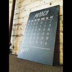 Chalkboard calendar on office wall  (gold frame maybe?)