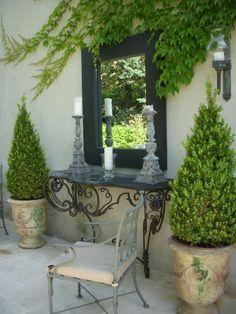 Un espejo en el porche sobre una consola potencia la luz natural del espacio y aporta un toque de sofisticación.