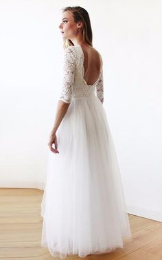 Effortlessly beautiful ivory tulle wedding gown. Bodice has an intricate soft lace design with 3/4 length sleeves. The skirt is made from the finest silk tulle, and has a floor-length hemline.A modest and feminine style that elegantly outlines the body, and comfortable to wear.Each maxi tulle and lace dress is crafted using two layers of high-end silk tulle, and features a quality viscose inner lining for comfort and flare. Paired with its relaxed fit and stunning craftsmanship, the m...