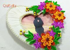 Find How to make this beautiful quilling photo frame at home by using cardboard, wool and quilling strips.