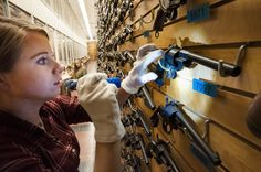 Julia Evans, a museum studies graduate student at the Quad Cities Campus of Western Illinois University, looks for a serial number inside of a revolver while conducting an inventory of the RIA Museum's small arms collection at Rock Island Arsenal, Illinois, Dec. 12.