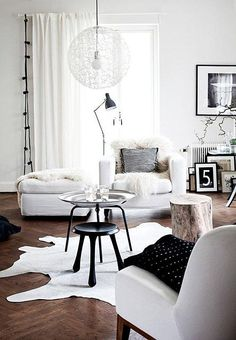 """Whiteout! Wood and black accents warm up this all-white living room in modern Scandinavian style. Read more and see them all on """"Our Favorite (Almost) All-White Rooms"""" over on our Style Guide!"""