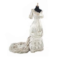 An 1870s cream silk satin wedding dress and a pair of 1860s cream satin boots With a deep V-neckline trimmed with later crocheted flowers, elbow-length sleeves, a deep asymmetric tabbed swag across the skirt front and a long train trimmed with heavily pleated frills and lace, labelled 'A. Matheson & Co., 39 Bridge Street, Edinburgh'