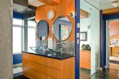 bathroom with royal blue paint, orange toned wood, round mirrors, glass vanity bowls (Pantone, Royal Blue)