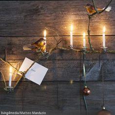 Eine Kombination aus Christbaumkugeln, brennenden Kerzen und Deko-Vögeln ist eine tolle DIY-Weihnachtsdeko. Schön drapiert auf einem Zweig strahlen die brennenden …