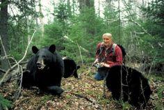 Lynn kneeling among bears recording data