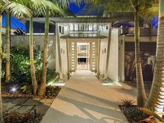 Photo of entrance into the modern villa with palm trees all around it