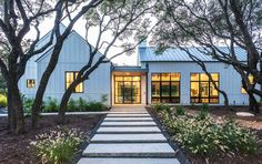 The roof of this modern farmhouse style home is Kynar, Galvalume from Taylor Metal Products. The exterior paint color is Sherwin Williams First Star. Modern farmhouse style in Texas showcases fantastic design inspiration Farmhouse Architecture, Modern Farmhouse Exterior, Modern Farmhouse Style, Farmhouse Design, Modern Architecture, White Farmhouse, Cottage Exterior, Texas Farmhouse, White Cottage