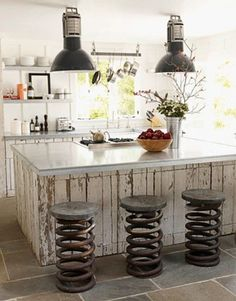 Eclectic mix of styles in this kitchen. I love the industrial look of the bar stools and overhead lights with the shabby white-washed counters