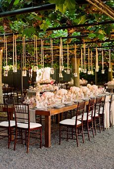 Long tables filled with flowers are set under a sycamore arbor hung with chandeliers and twinkling lights