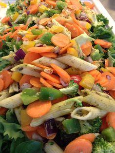 Blandet grøn salat pasta penne vendt i pesto broccoli i buketter snak gulerødder i tynde skiver peberfrugter i små tern rødløg i tern Kom den grønne salat i bunden af et fad, ven de andre ting sammen og fordel det over salaten.