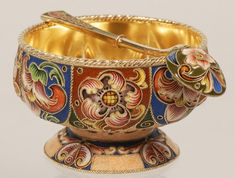 A Russian gilded silver and cloisonné enamel open salt with matching spoon by Feodor Ruckert, Moscow, 1908-1917. The raised, lobed bowl is extensively decorated with alternating scrolling floral motifs in vibrant shaded enamel against either a brick red or blue ground. The circular domed foot is similarly enameled, as is the matching spoon. Marked with the 88 silver standard and an inventory number.