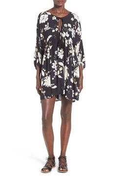 A bold floral print blooms across a swingy babydoll dress with a tassel-tie neckline, three-quarter-length blouson sleeves and a subtle high/low hem that moves gracefully with each step.
