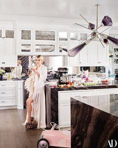 Jenner—wearing a vintage robe, an LPA bodysuit, and Shay Fine Jewelry—in her kitchen. Blown-glass chandelier by Gabriel Scott; custom cabinetry by Martyn Lawrence Bullard.
