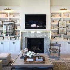 Alice Lane Home Collection | Family room with marble and brass fireplace surround, built-in bookcases.