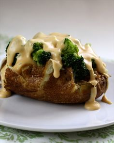 Easy Baked Potatoes topped with steamed broccoli and an AMAZING Cheese Sauce! Don't leave out that {not so} secret ingredient- it MAKES the sauce!!