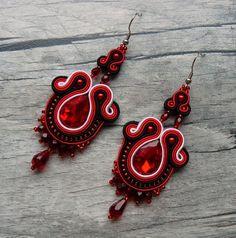 Krvavé+slzy+Sutaškové+náušnice+vytvořené+časově+náročnou+technikou+sutaškování.+Střed+náušnice+je+tvořen+skleněnou+broušenou+slzou+v+červené+barvě.+Na+výrobu+byly+dále+použity+textilní+prýmky+(sutašky)+ve+černé+a+červené+a+stříbrnébarvě+a+voskové+perličky+v+červené+barvě.+Na+dozdobení+byly+použitybroušené+korálky+-+slzy,+ohňovky+a+kvalitní...