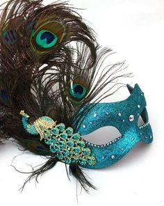 Feathered half mask trimmed in neads and sequins. Halloween, costume. Masquerade weddings are gaining popularity and have almost become a cool trend, they are агт at any time of the year but especially if you are having a Halloween wedding.
