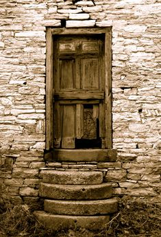 Monochromatic image of a wooden door within it's rocky surroundings. ...Great texture and contrast.